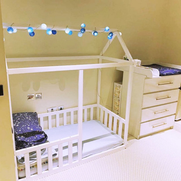 A toddler bed with rails, decorated with a lighting chain.