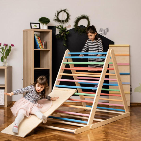 A girl sliding down a triangle climber toy with a slide board