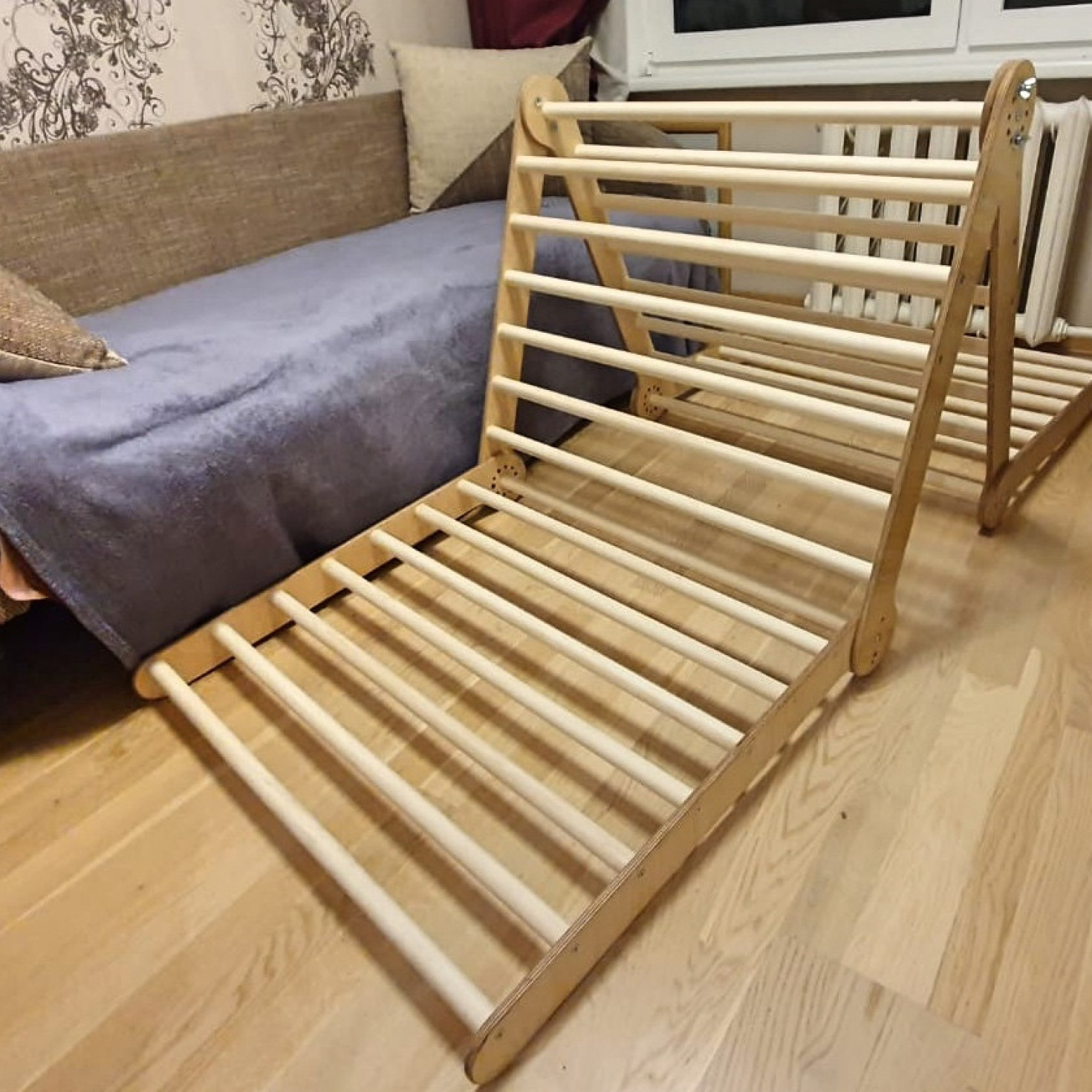 A wooden climbing frame next to a couch
