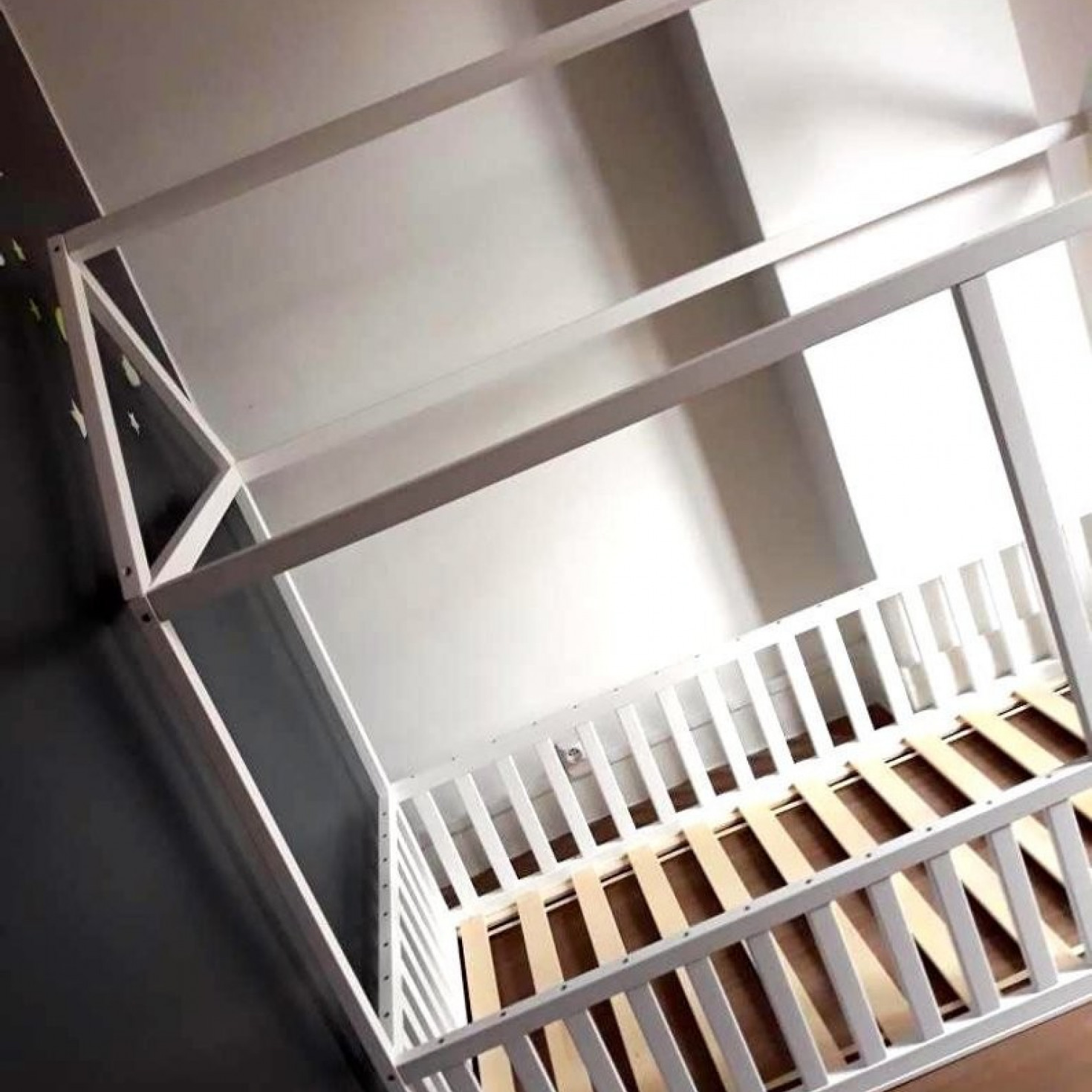 A toddler house bed frame with rails