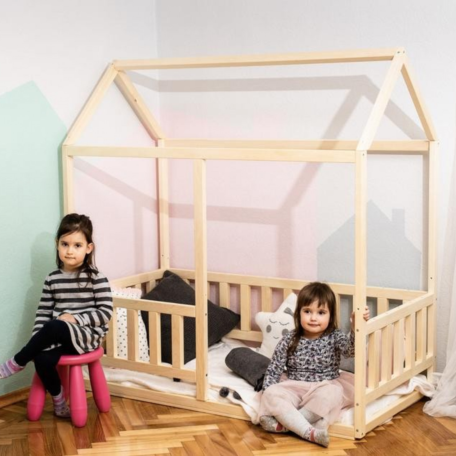 Children posing next to a toddler floor bed