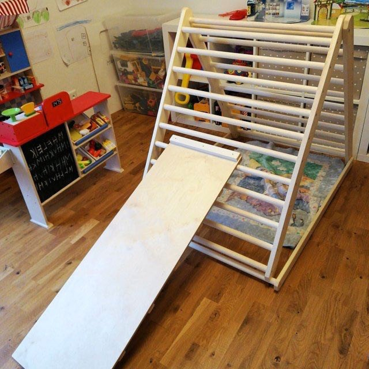 A children's wooden climbing frame with a slide board