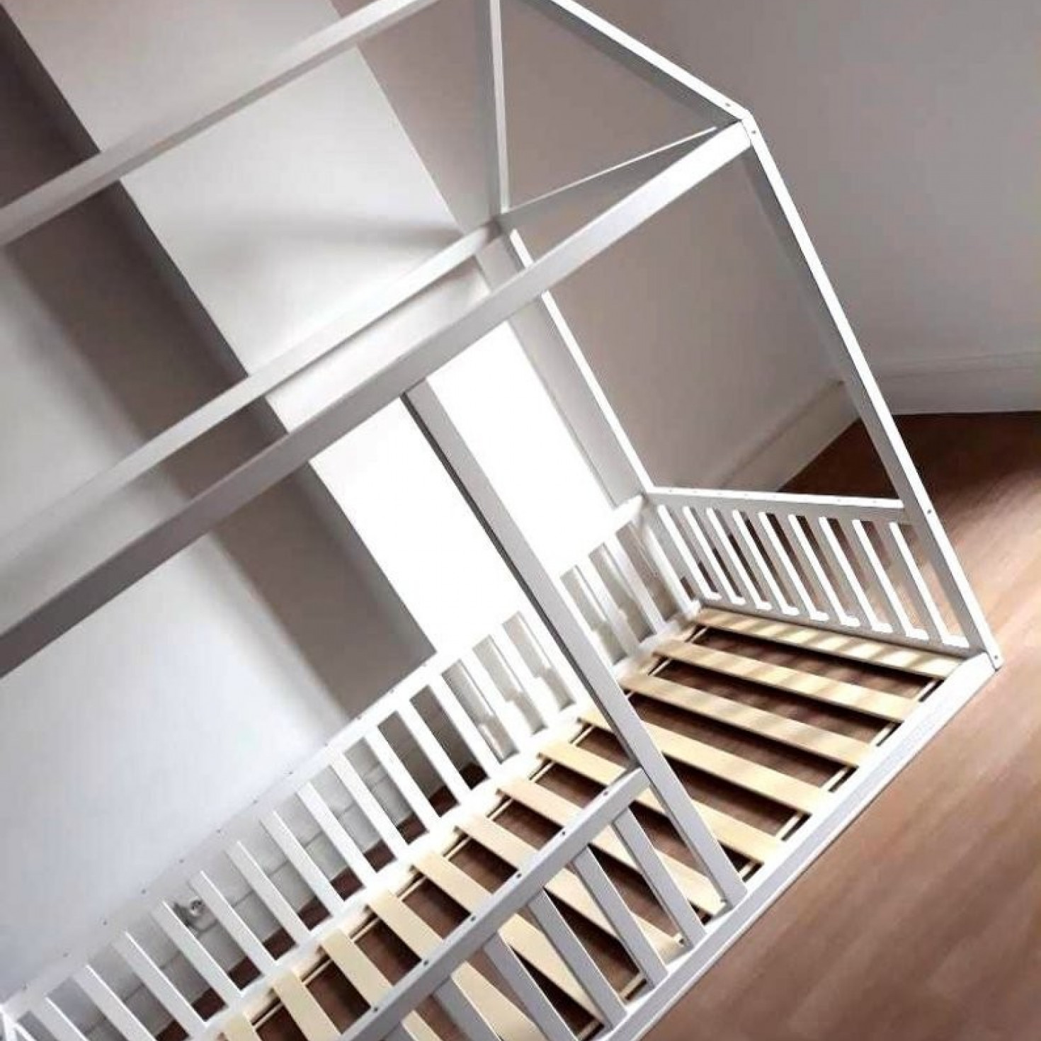 A toddler bed frame with rails all around