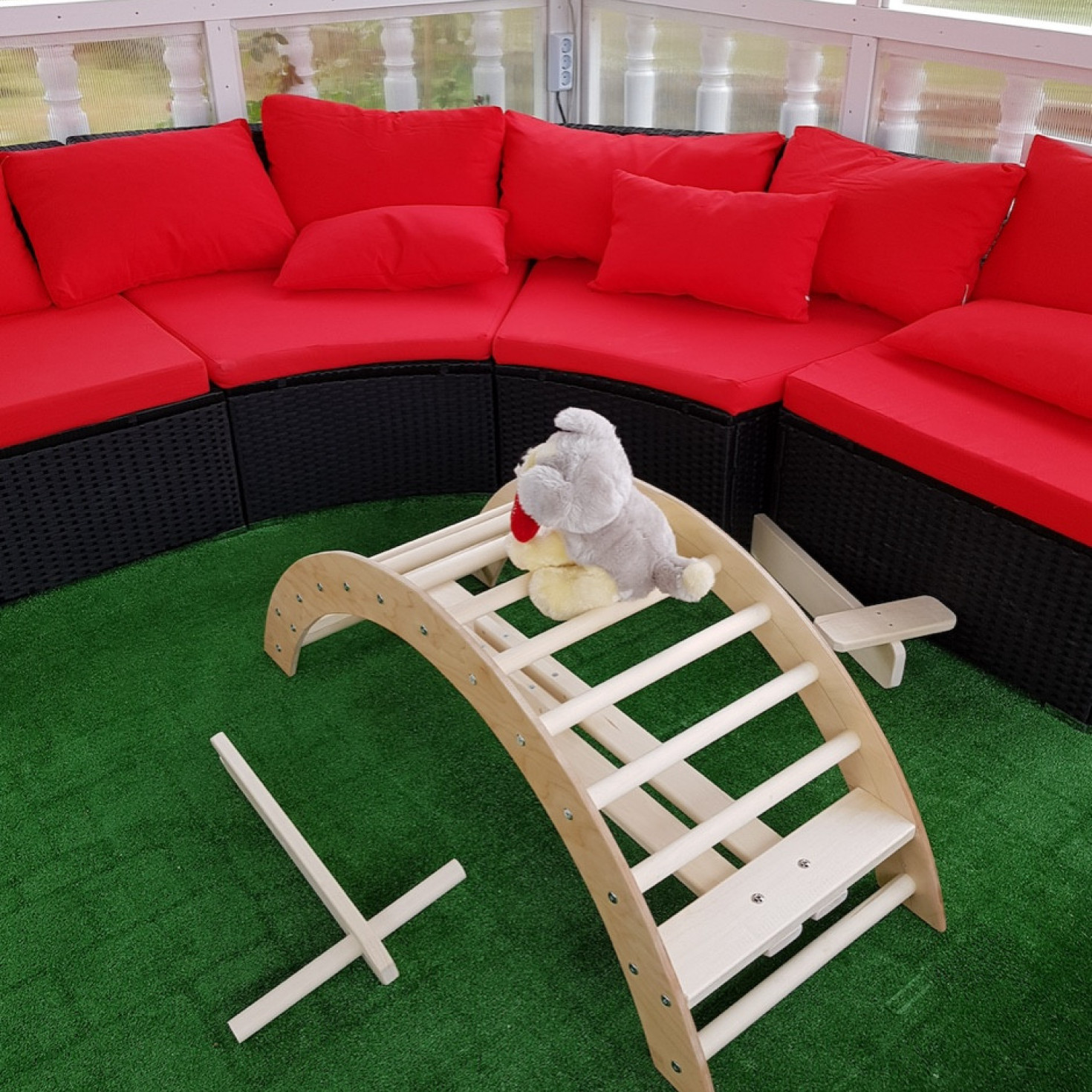 A wooden climbing arch next to a red couch