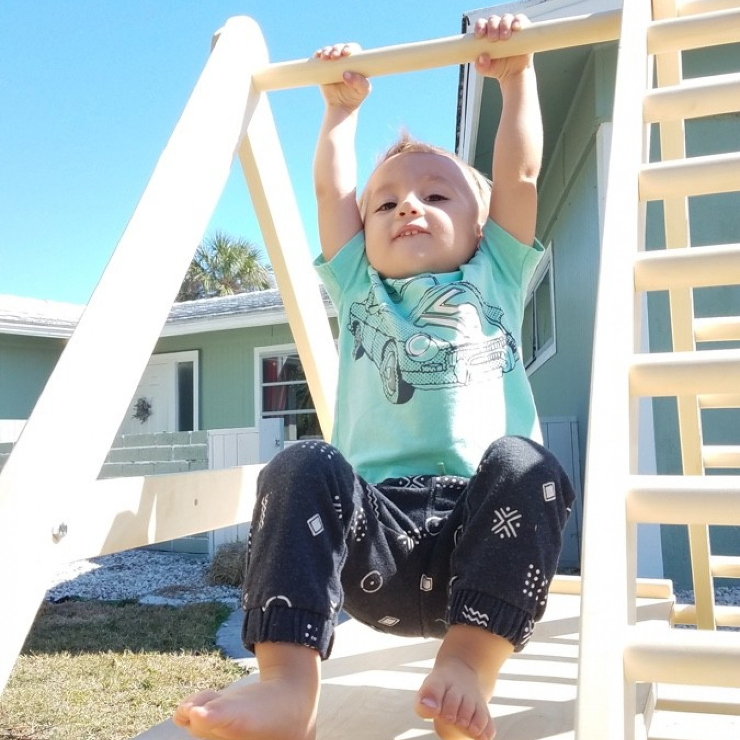 A child hanging on a climbing ladder for toddlers