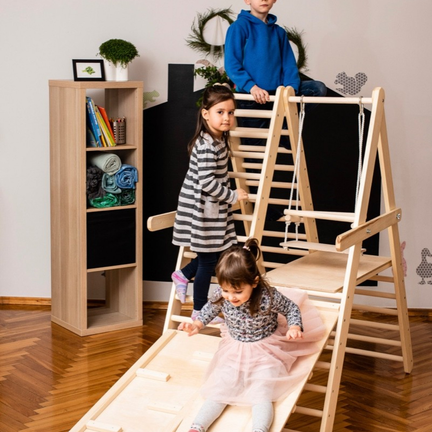Children using a climbing triangle for toddlers with a slide board