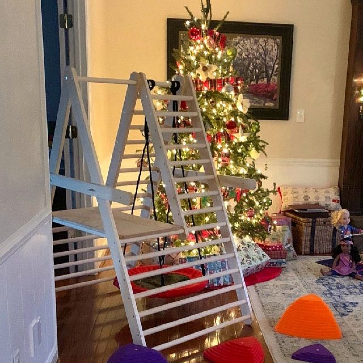 A climbing ladder for toddlers next to a Christmas tree