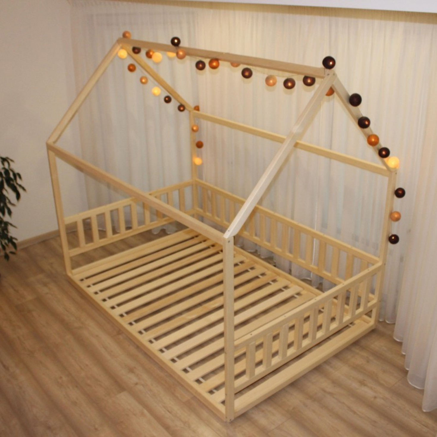 A toddler floor bed frame decorated with a lighting chain