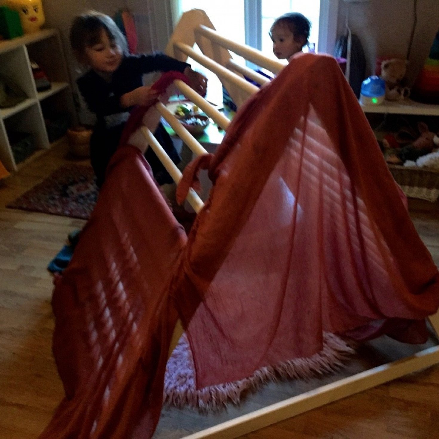 Children playing with an indoor wooden climbing frame