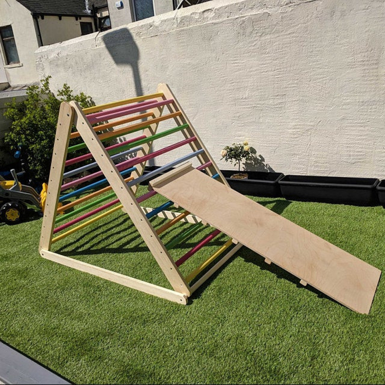 A rainbow-colored wooden climbing frame placed in a garden