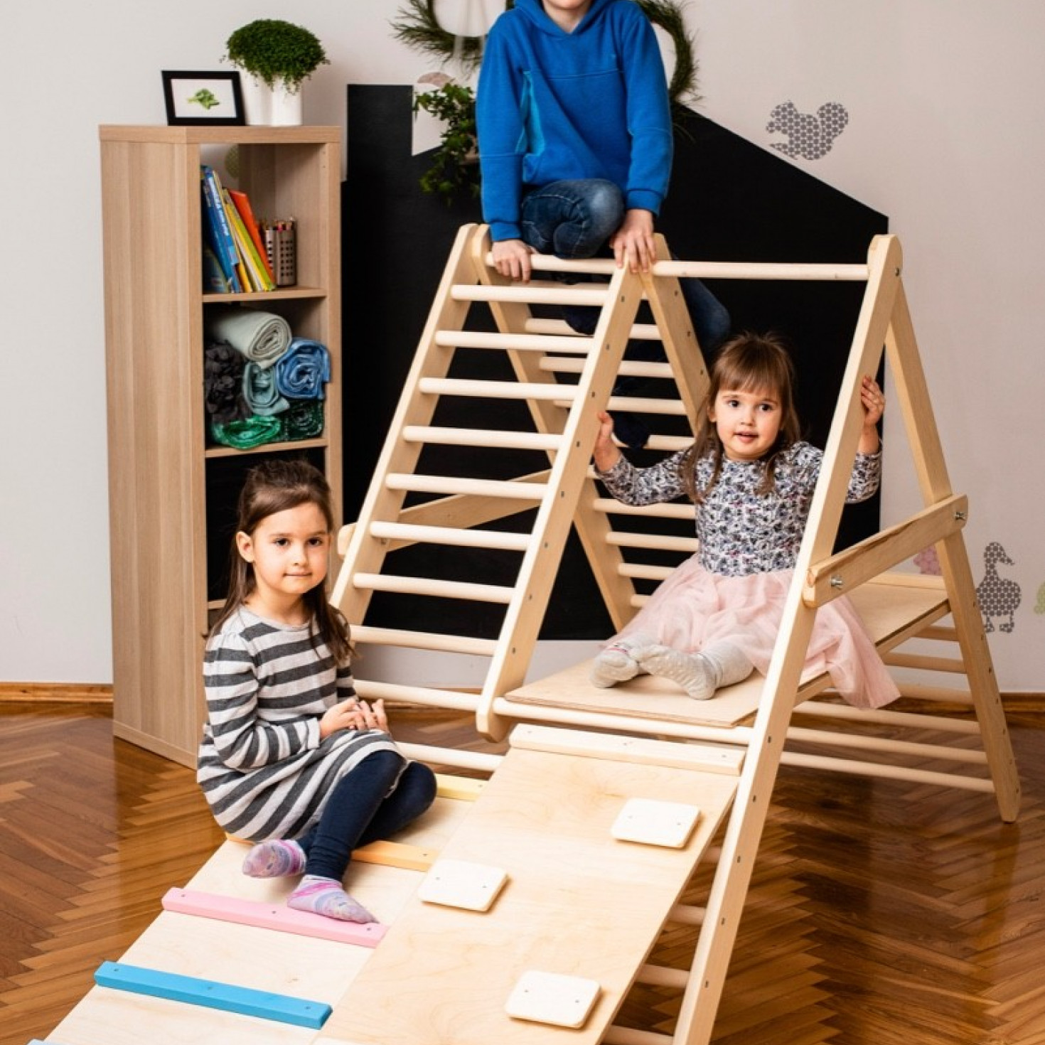 Pre-schoolers playing on a climbing ladder