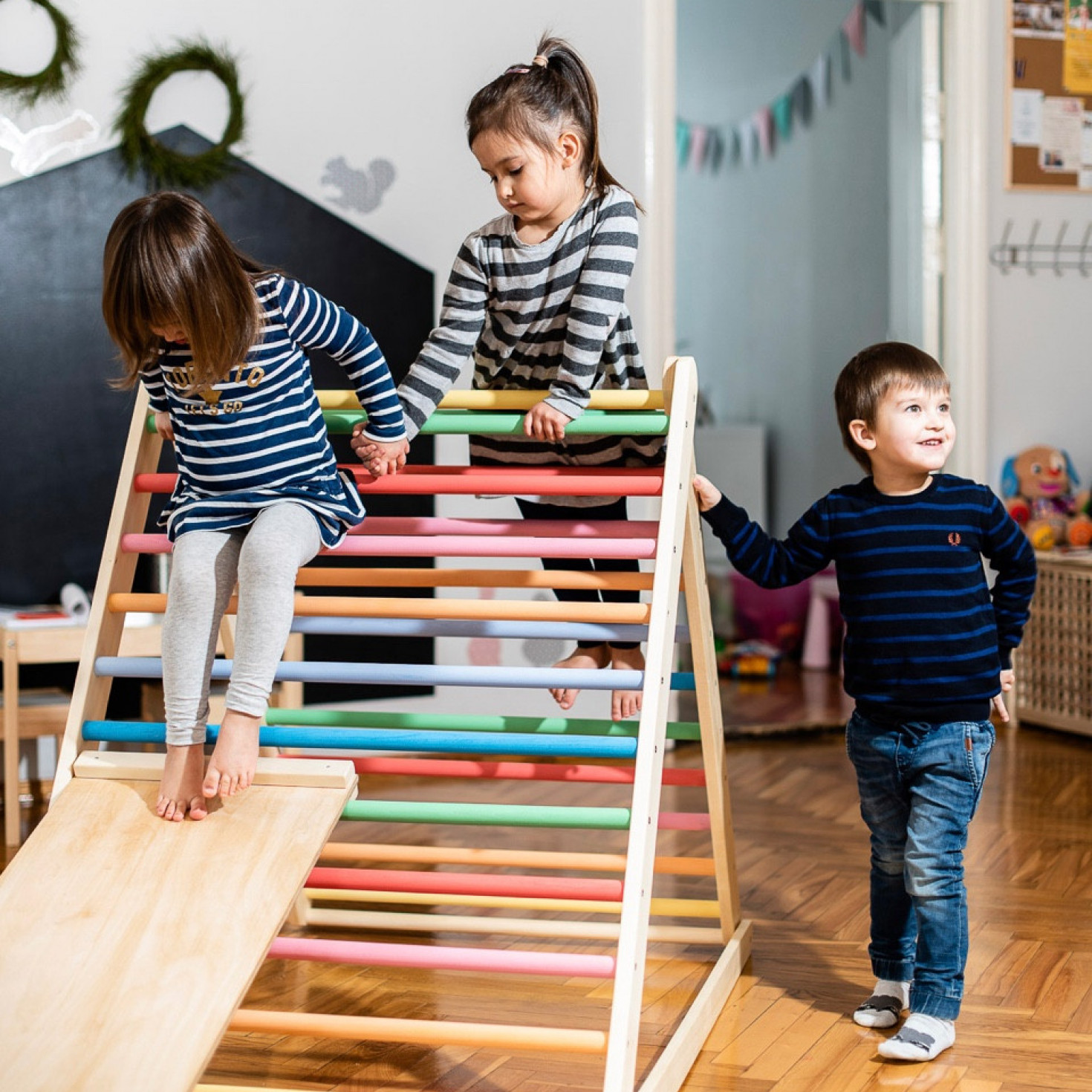 Children playing on a wooden climbing frame for toddlers