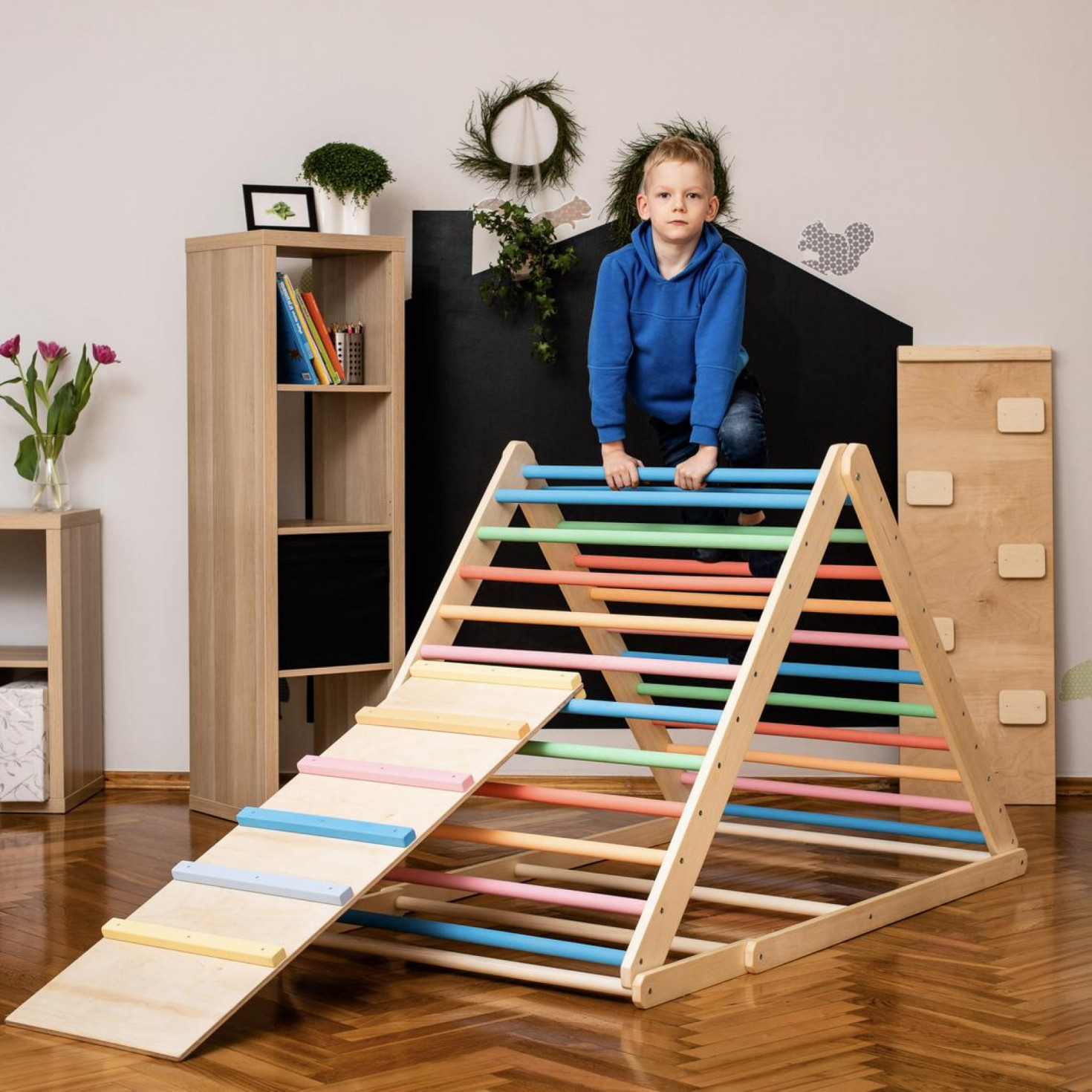 A child standing on a wooden triangle climber with rainbow-colored rungs
