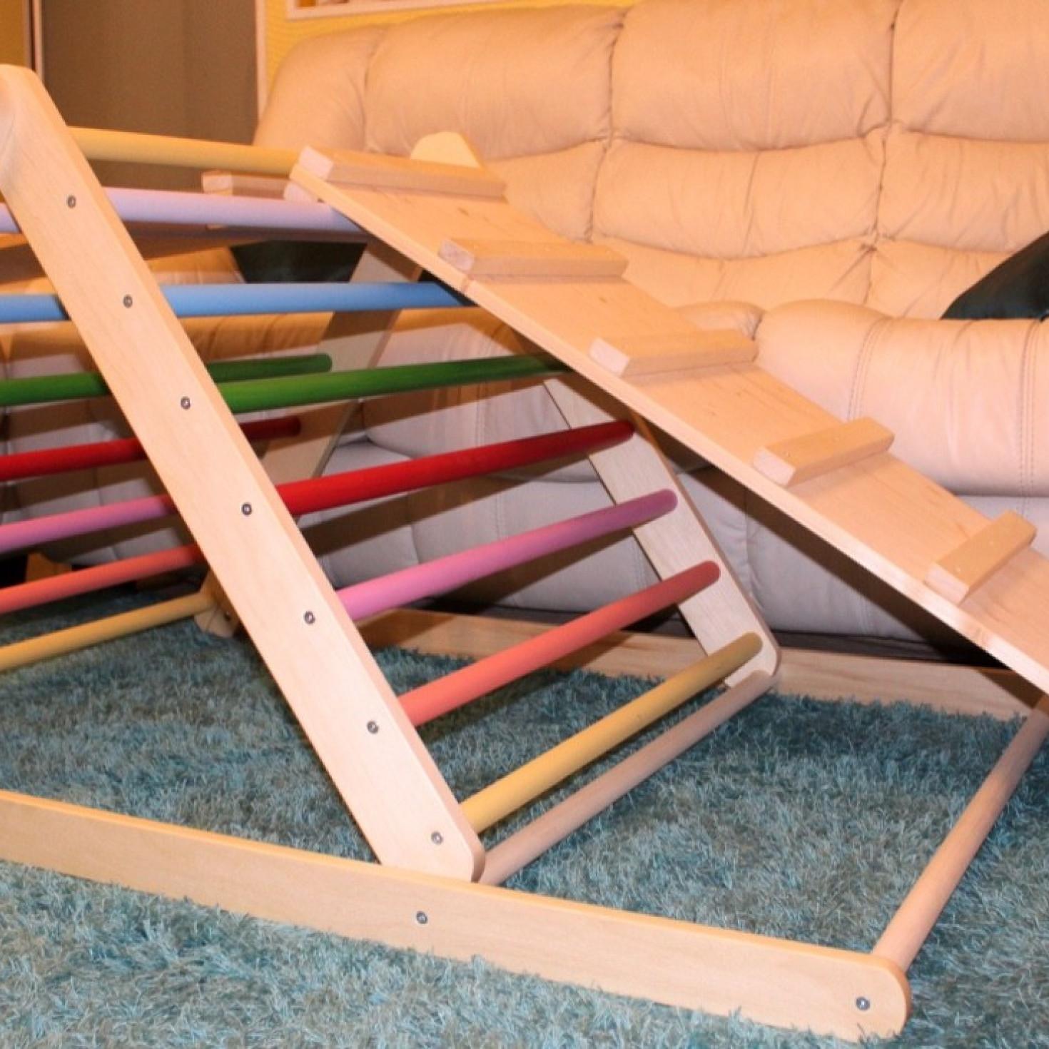 A Pikler triangle with ladder and slide boards placed in a living room